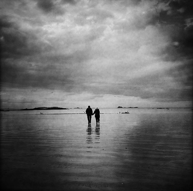 The couple on the beach, Saint-Malo, Brittany. This elderly couple, hand in hand, were walking together to the sea, to the same horizon. A single moment of great beauty and complicity.