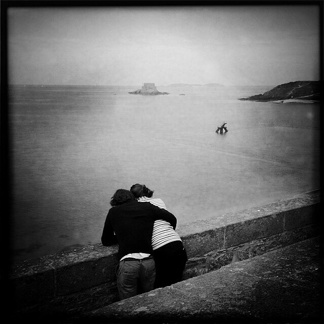 Lovers, Saint-Malo, Brittany. At high tide, alone, entwined, these two lovers enjoyed a quiet moment and the beautiful view of the horizon. By the sea, solo, as a couple, in family or just among friends, we look and allow our mind to wander.