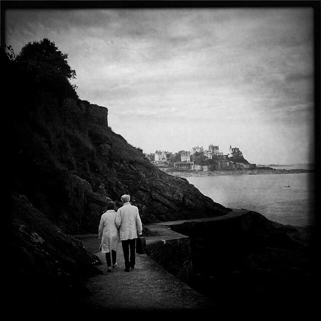 """Walk in the Moonlight"", Dinard, Brittany. This couple takes the romantic stroll ""Walk in the Moonlight"". I liked these two figures who were walking side by side, at a leisurely pace, dressed in raincoats of the same color. Together, happy, blend in with the landscape, out of time."